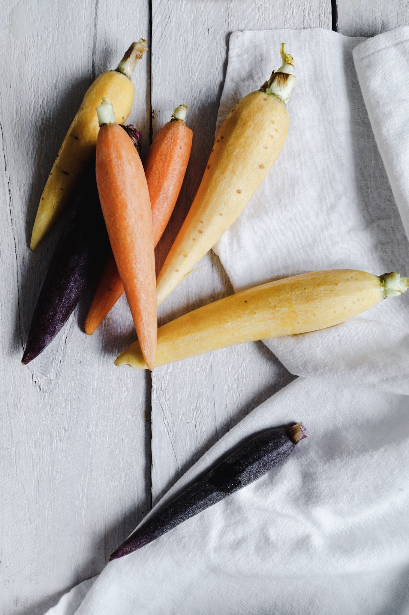 Colorful carrots in minimal light and bright food photography and styling with some ideas for a spring veggie tray.