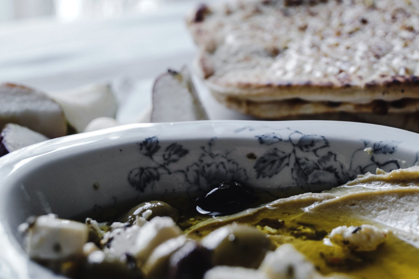 Naan with hummus and marinated olives for dipping.