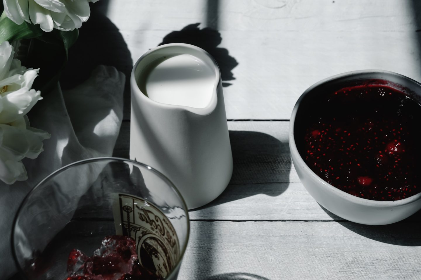 A delightfully tiny creamer sits by a bowl full of jam ready to be poured over our French soda.